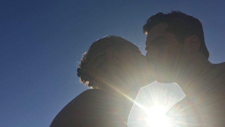 Belén Rueda y Francis Malfatto besándose con el sol de fondo