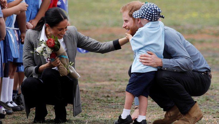 Meghan Markle ríe divertida mientras un niño toca la barba del Príncipe Harry