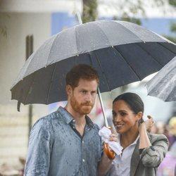 El Príncipe Harry y Meghan Markle con un paraguas en Australia