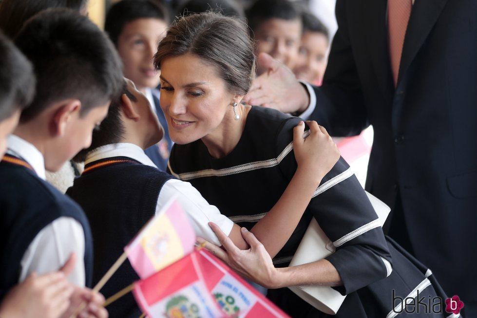 La Reina Letizia, muy cariñosa con un niño del colegio Reino de España de Lima