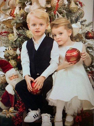 Jacques y Gabriella de Mónaco posando frente a un árbol de Navidad