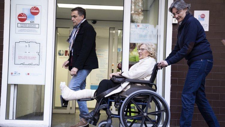 Manuela Carmena en silla de ruedas saliendo del hospital