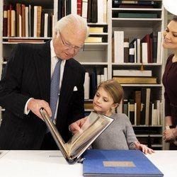 Carlos Gustavo de Suecia enseña un libro a Estela de Suecia junto a Victoria de Suecia en la Biblioteca Bernadotte