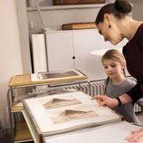 Victoria de Suecia enseña a su hija Estela unas fotos familiares antiguas en la Biblioteca Bernadotte