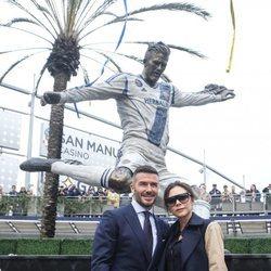 David Beckham y Victoria Beckham posan junto a la estatua del futbolista