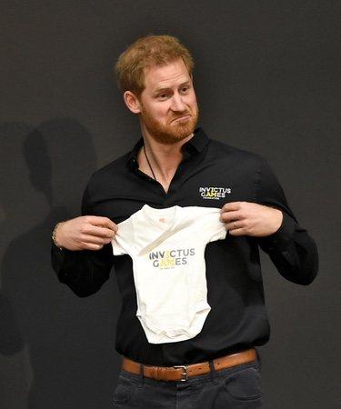 El Príncipe Harry con el body para su hijo Archie Harrison