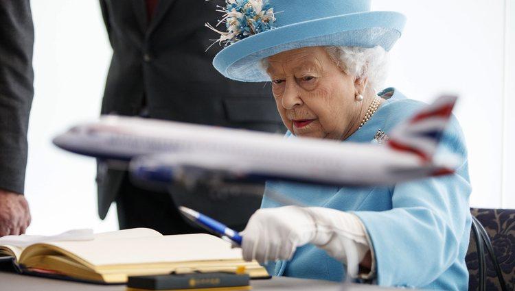 La Reina Isabel firmando el libro de visitas del aeropuerto de Heathrow