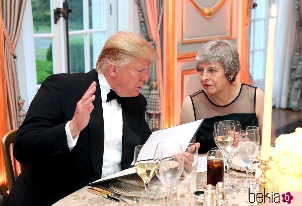 Donald Trump charla con Theresa May durante la cena en la embajada de EEUU en Reino Unido