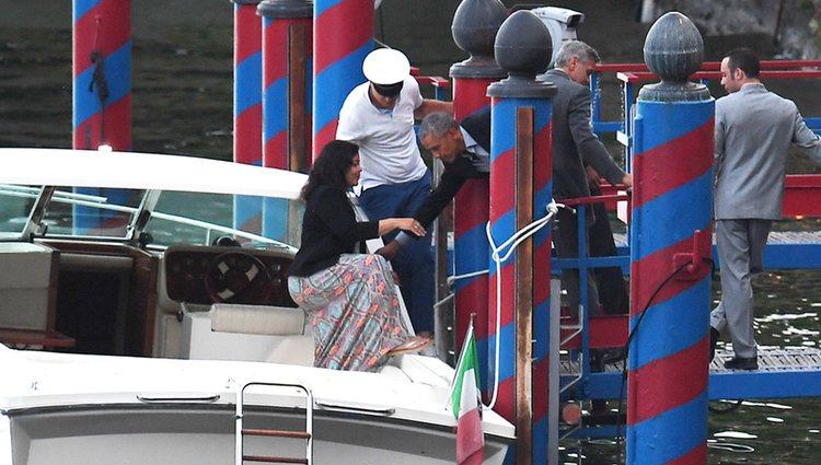 Barack Obama ayudando a su esposa Michelle