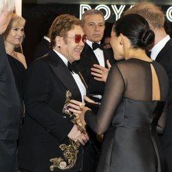 El Príncipe Harry y Meghan Markle saludando a Elton John en el estreno de 'El Rey León' en Londres