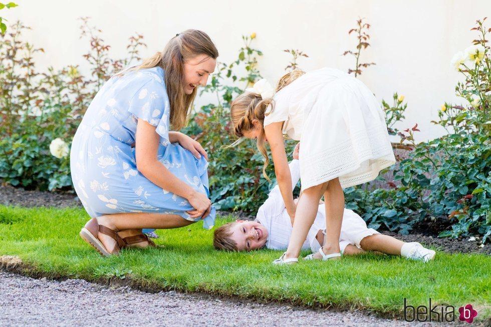 Estela y Oscar de Suecia jugando con su niñera en el Palacio de Solliden
