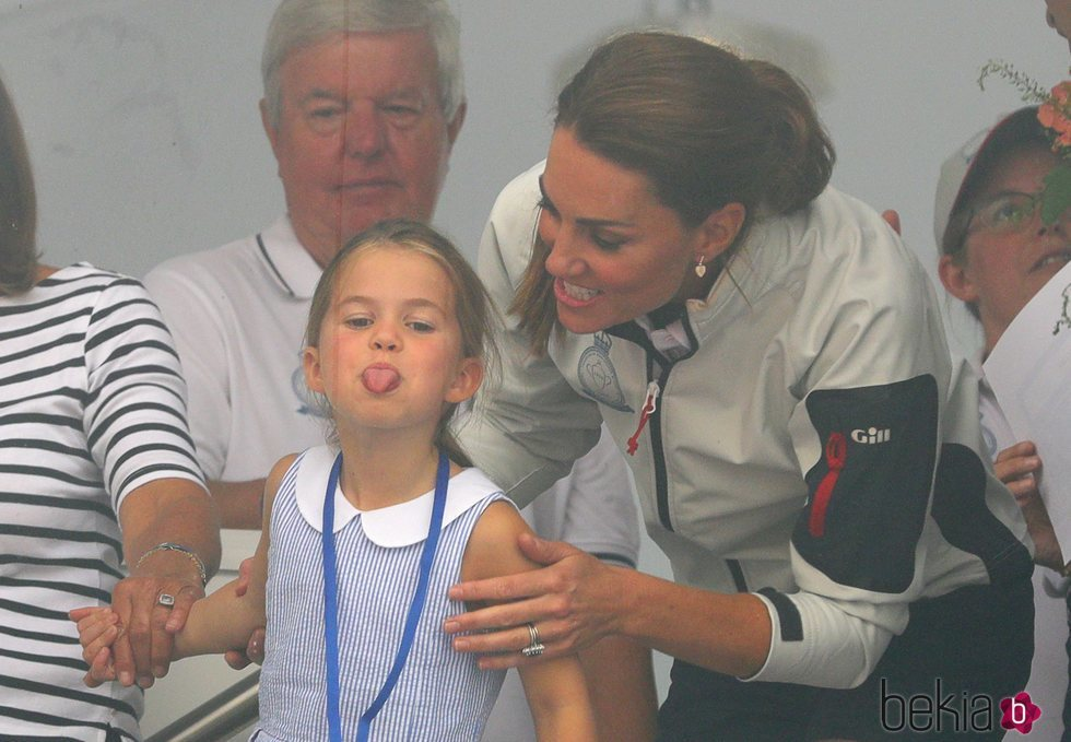 La Princesa Carlota sacando la lengua ante la mirada risueña de su madre