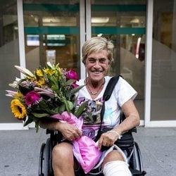 Chelo García Cortés saliendo del hospital con un ramo de flores