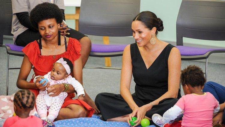 Meghan Markle con una mujer y unas niñas en su visita a Mothers 2 Mothers en Sudáfrica