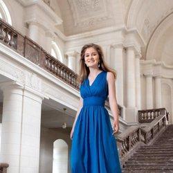 Isabel de Bélgica con un vestido azul en las escaleras de Laeken