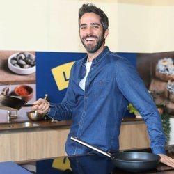 Roberto Leal sostiene una sartén en un evento de cocina