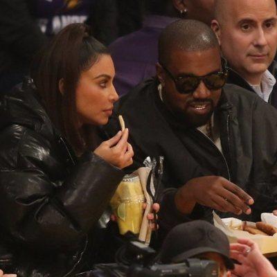 Kim Kardashian y Kanye West comiendo en un partido de baloncesto