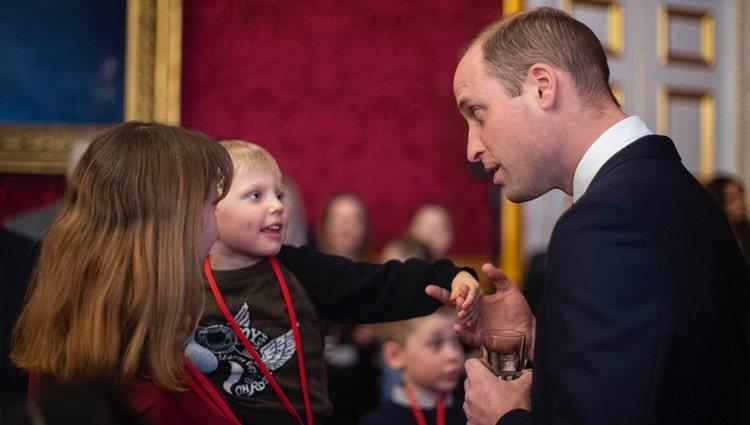 El Príncipe Guillermo con un niño en una recepción en St James Palace