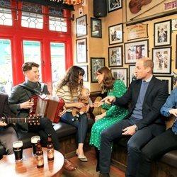 El Príncipe Guillermo y Kate Middleton charlando con unos músicos en un pub de Galway