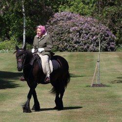 La Reina Isabel montando en caballo en los jardines de Windsor