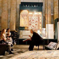 Victoria de Suecia y sus hijos Estela y Oscar de Suecia escuchan explicaciones en una exposición de alfombras