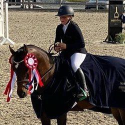 Emma Tallulah Behn con su caballo en una competición hípica