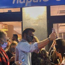 Can Yaman saludando a sus fans en la salida de una pizzería de Milán