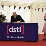 La Reina Isabel mira cómo firma el Príncipe Guillermo en su vuelta a los actos oficiales desde el confinamiento