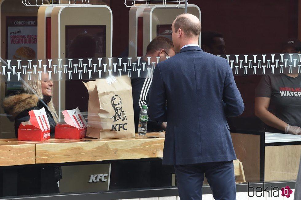 El Príncipe Guillermo mirando al interior de un KFC de Londres