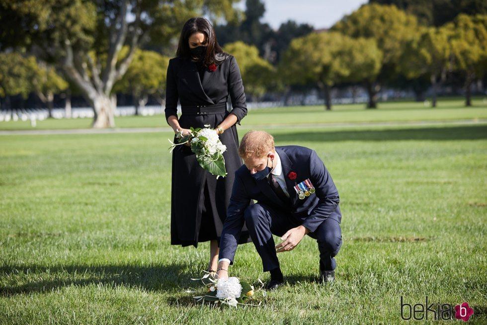 El Príncipe Harry y Meghan Markle depositando flores el Día del Recuerdo 2020