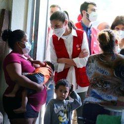 La Reina Letizia escucha a una mujer refugiada en un albergue en su viaje humanitario a Honduras