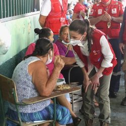 La Reina Letizia escucha el testimonio de una persona refugiada en un albergue en su viaje humanitario a Honduras