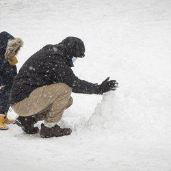 Dos ciudadanos haciendo un muñeco de nieve tras la gran nevada de Madrid de 2021 provocada por Filomena