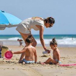 Irene Rosales echa protector solar a sus hijas en la playa