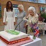 La Reina Isabel cortando una tarta junto a Camilla Parker y Kate Middleton en 'The Big Lunch' en la Cumbre del G7 en Cornualles