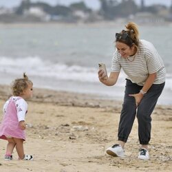 Toñi Moreno, haciendo una foto a su hija Lola en la playa