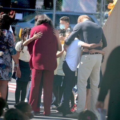 Meghan Markle y el Príncipe Harry abrazando a varios alumnos durante una visita a una escuela de Nueva York