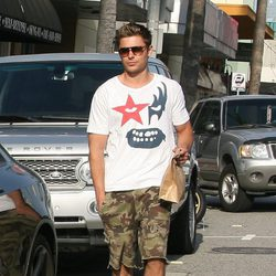 Zac Efron con gafas de sol y pantalones militares