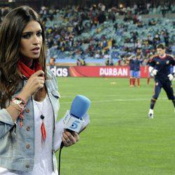 Sara Carbonero a pie de campo con Iker Casillas entrenando detrás