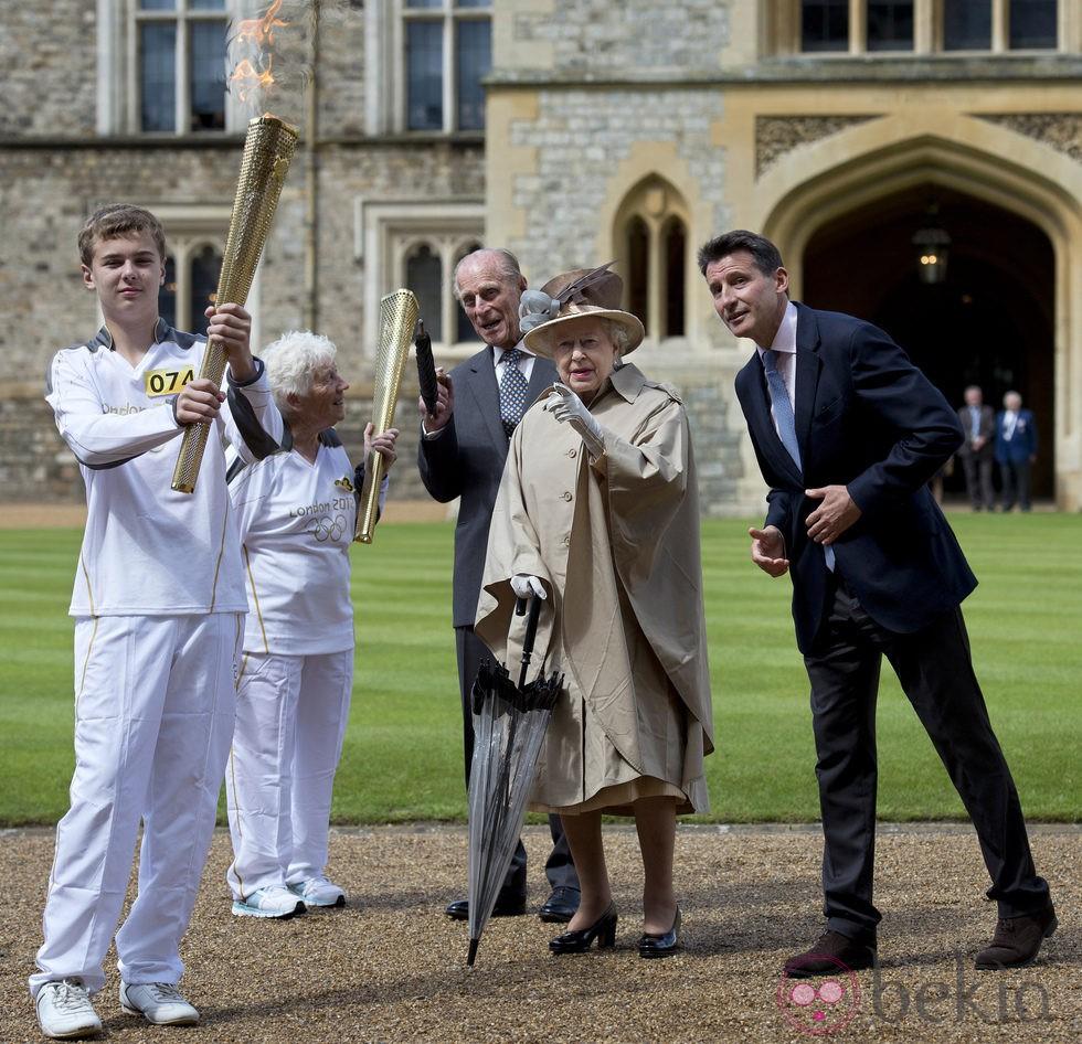 La Reina Isabel II de Inglaterra junto a la antorcha Olímpica de los JJ.OO de Londres 2012