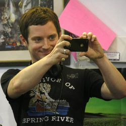 Elijah Wood sonríe con su iPhone