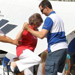 El Príncipe Felipe ayuda a la Reina a bajar de un barco en el segundo día de regatas 2011