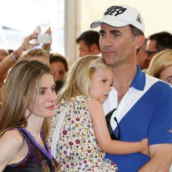 Don Felipe sostiene a la Infanta Sofía junto a Doña Letizia en el concierto de Jaime Anglada