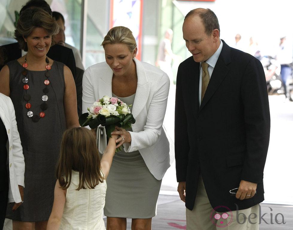 Charlene recibe un ramo de flores bajo la atenta mirada de Alberto de Mónaco