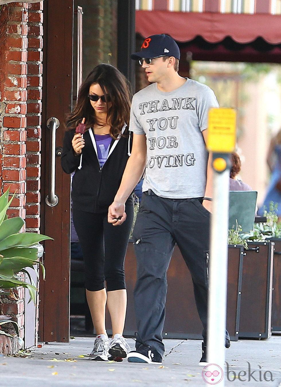 Mila Kunis y Ashton Kutcher comiendo un helado mientras pasean