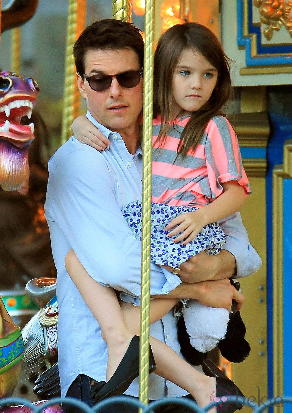 Tom Cruise con Suri en brazos en un tiovivo