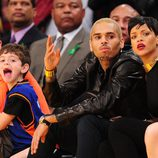 Rihanna y Chris Brown viendo concentrados el partido de la NBA