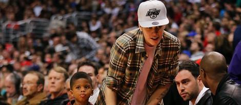 Justin Bieber con un niño de la mano en la NBA
