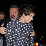Harry Styles es ayudado por un guardaespalda a la salida de su cumpleaños
