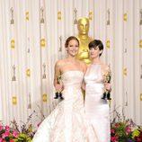 Jennifer Lawrence y Anne Hathaway posando con sus galardones en los Oscar 2013